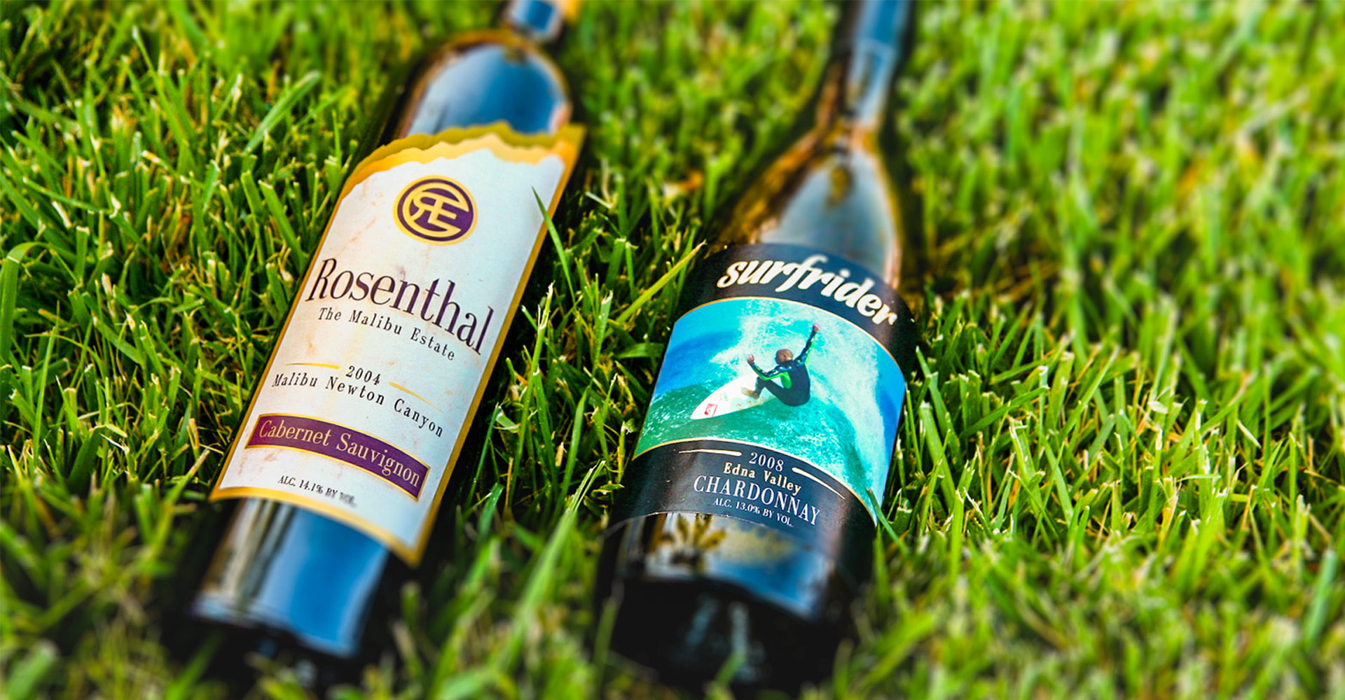 Bottles of Rosenthal and Surfrider wines laying in the grass
